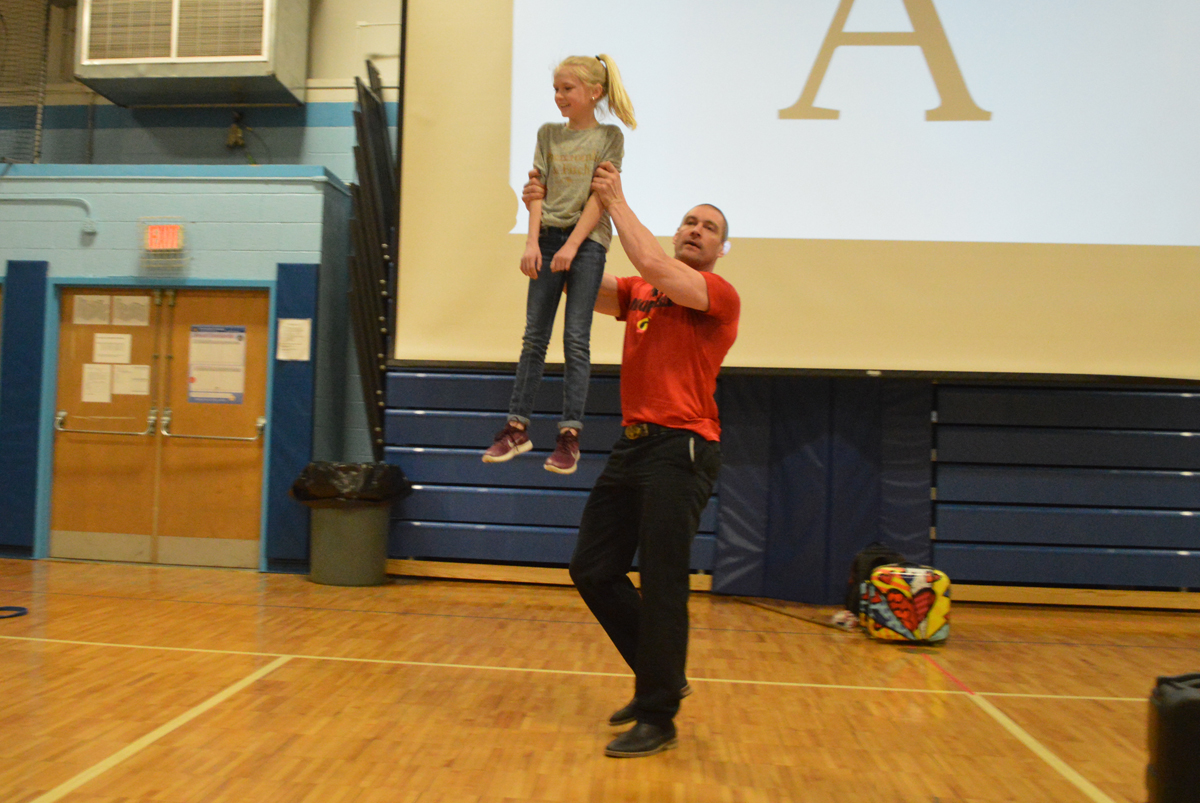 Tom Murphy lifts up student