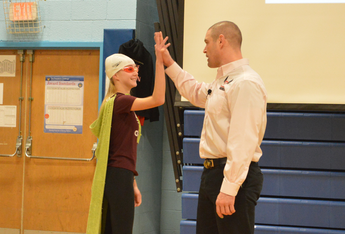 A student gives high five to Tom Murphy during Sweethearts & Heroes presentation