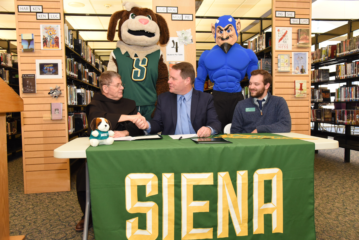 Siena President Br. Ed Coughlin, O.F.M., shakes hands with Superintendent Jeff Simons