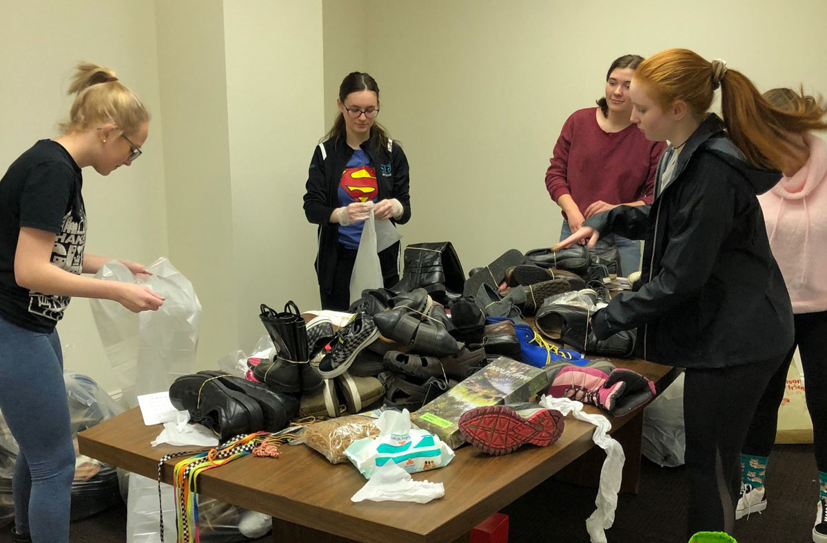 Students sorting shoes for donation