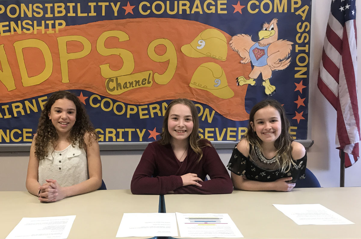 Mallory Paschall, Riley Hauenstein, and Lilliana Larson reporting morning announcements at DPS