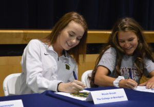 Students signing college commitment letters