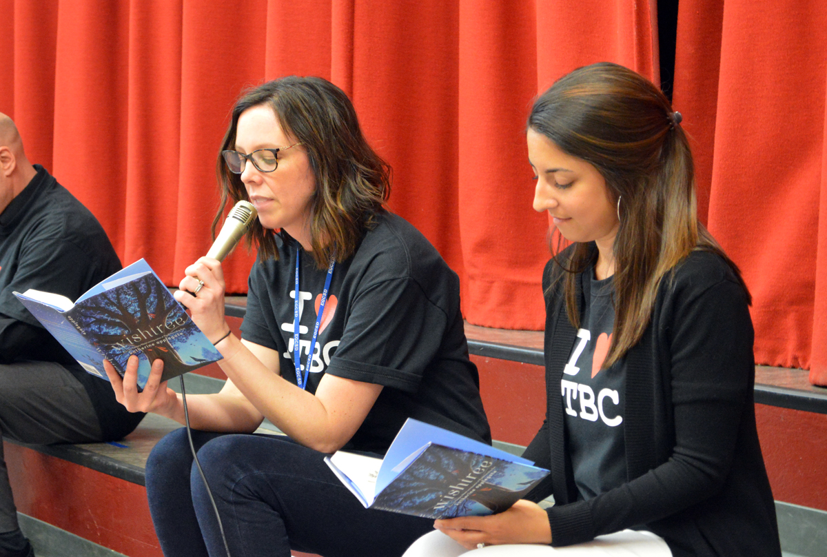 Teachers reading a book to students