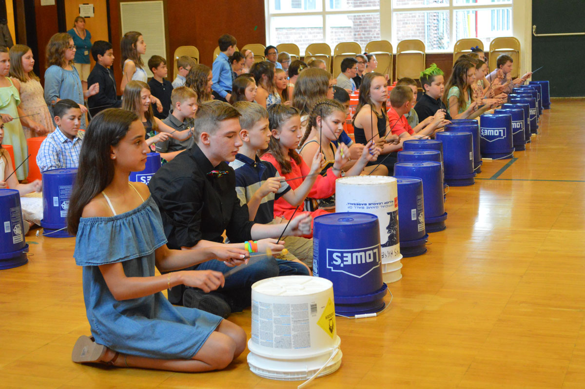Students drumming on buckets at the Green Meadow Moving Up Ceremony