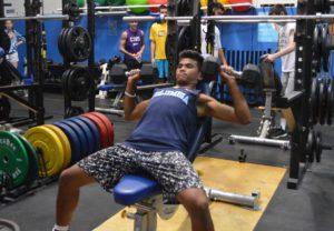 Student lifting weights at summer training program