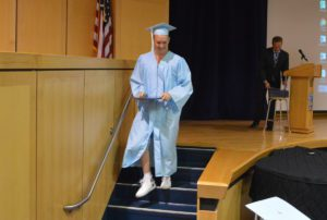 Graduate walks off stage with his diploma