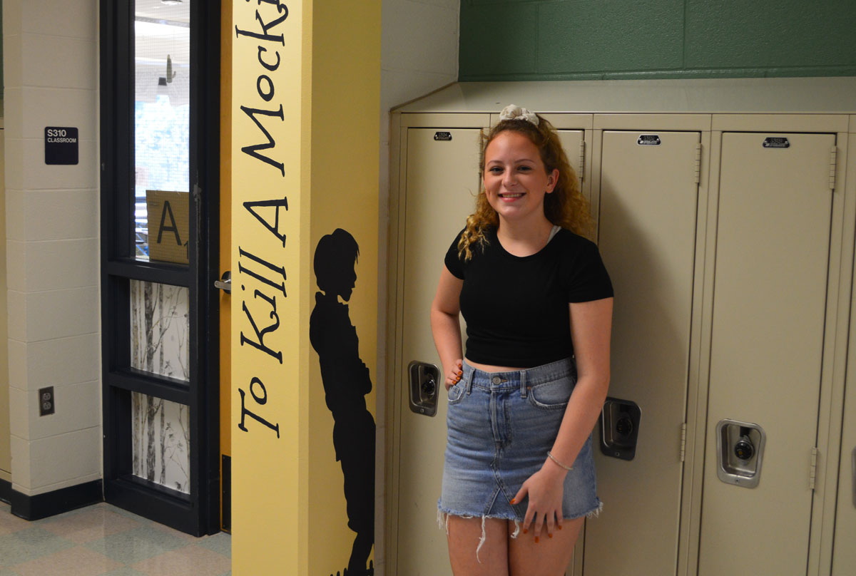 Bella Dupont standing beside a book mural she created at Columbia High School