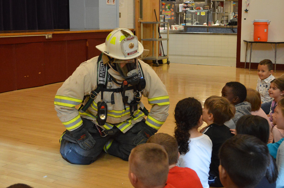 Firefighter talks with students