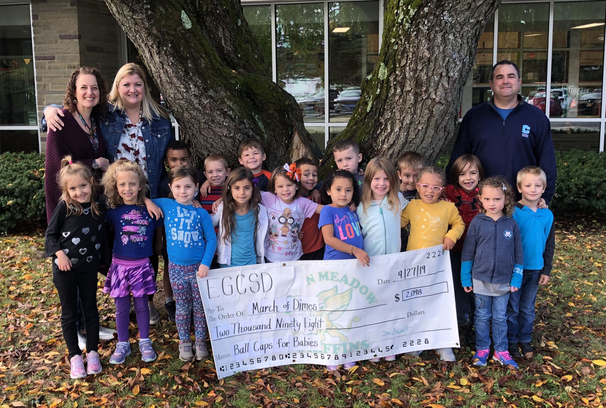 Students and teachers hold donation check