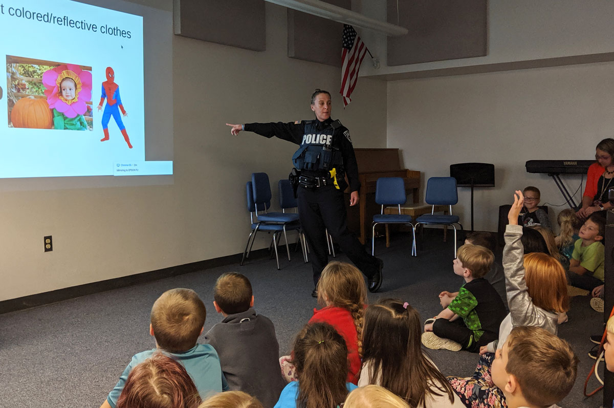 Officer Abraham giving Halloween safety presentation at Red Mill