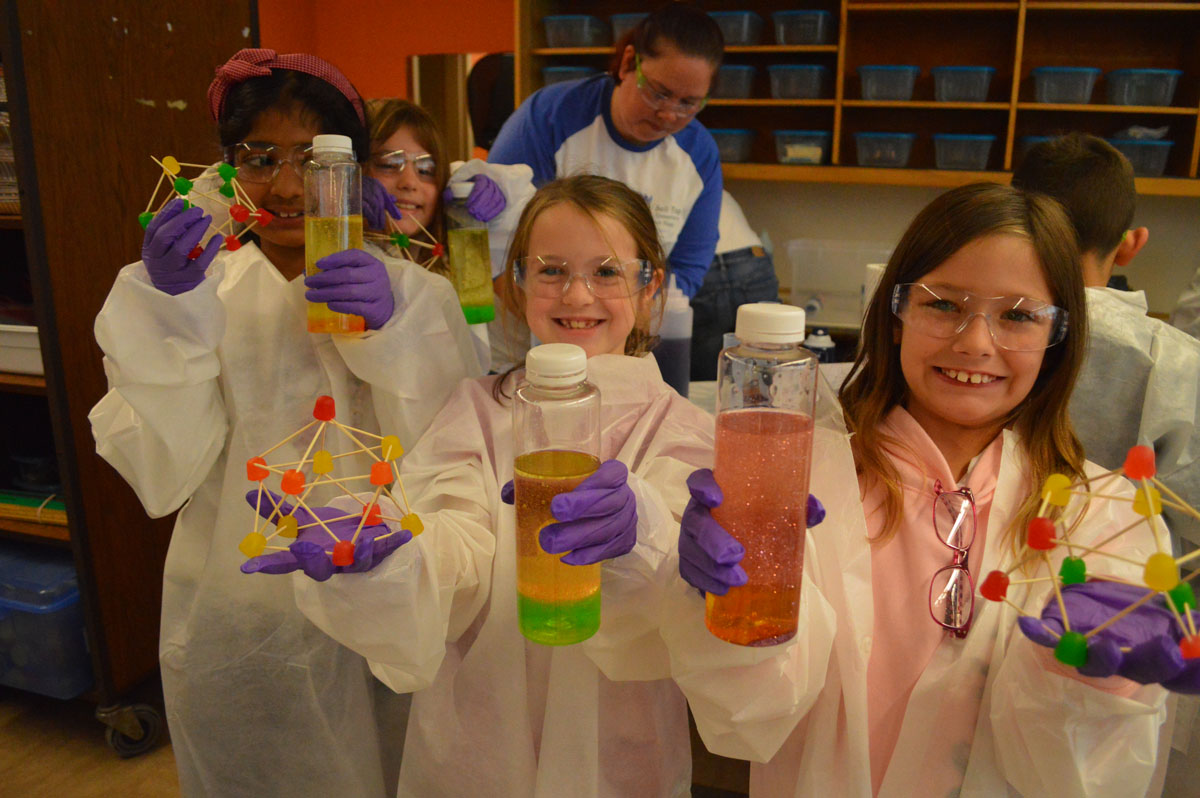 Students hold up science experiments