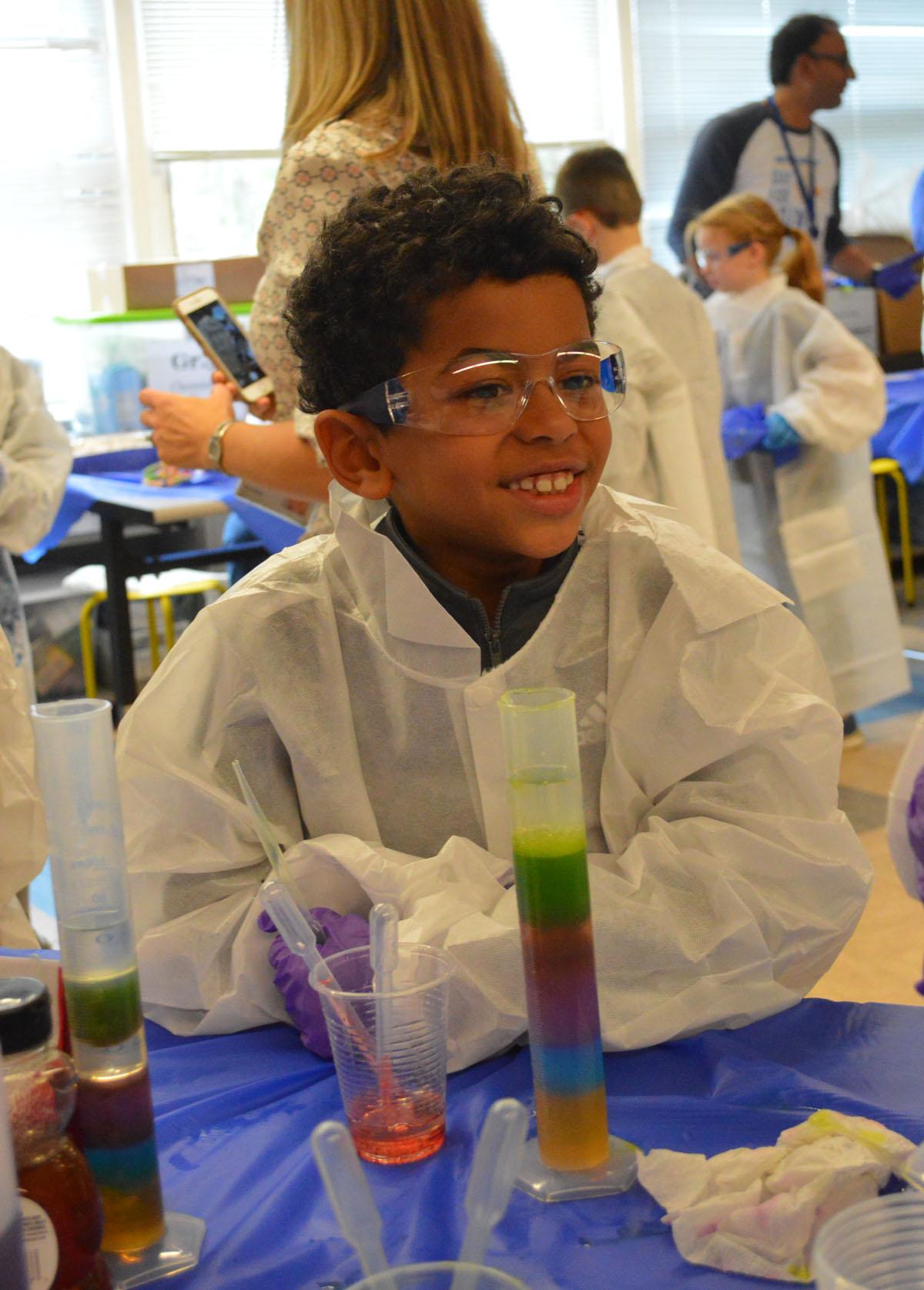Student in lab coat smiling