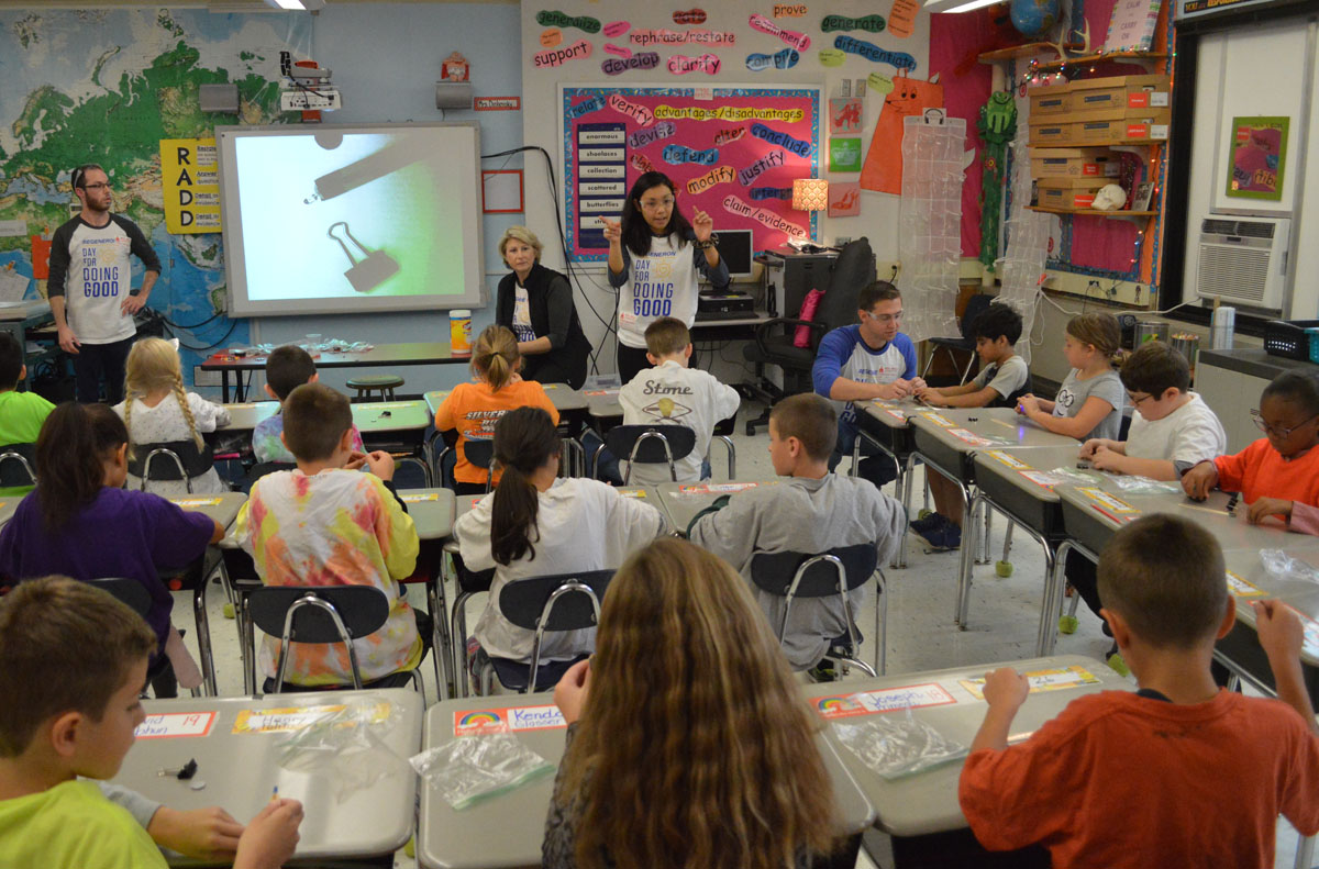 Regeneron volunteer leading experiment at front of classroom