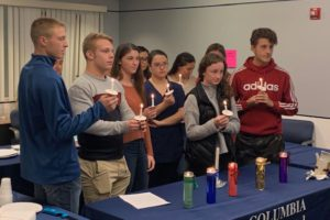 Columbia students light candles at Rho Kappa National Honor Society induction ceremony