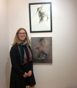 Alison Hosier stands next to her artwork at Faculty Art Show