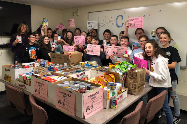 Students in Mrs. VanAlstyne's 6th period class donate boxes of cans