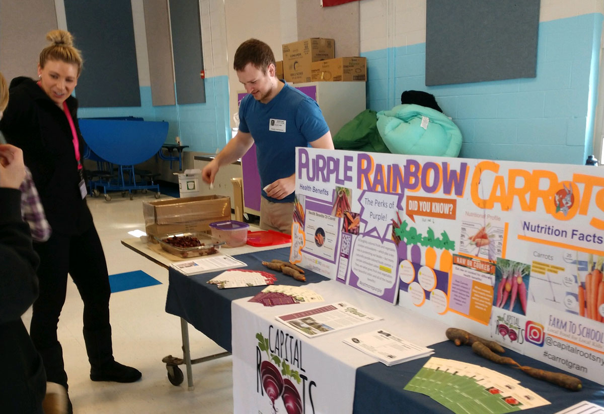 Scott Fuller from Capital Roots serves different varieties of carrots to Goff students and staff at Goff Middle School