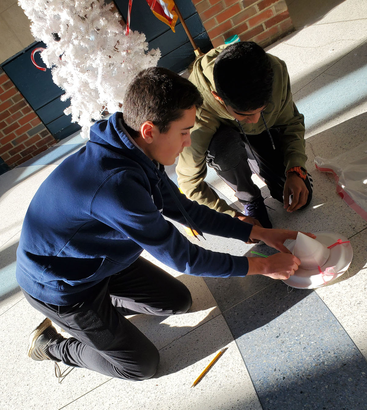 Students work on their egg drop cradle