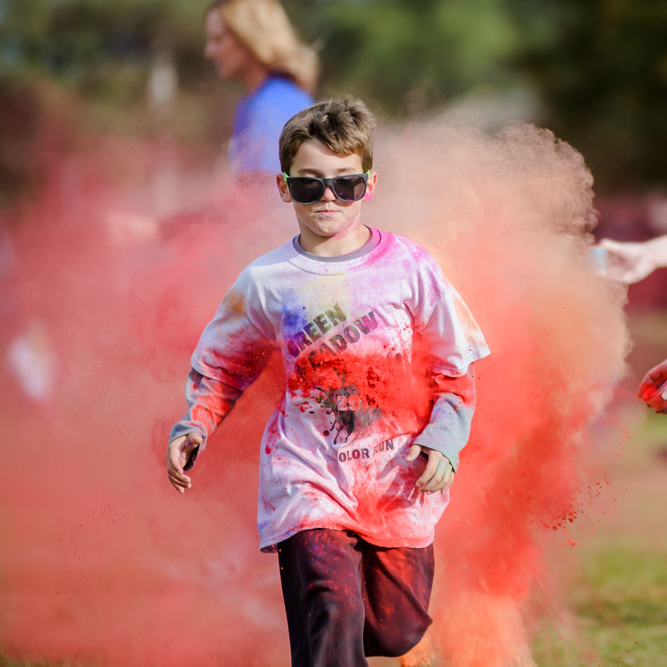 Student running in Green Meadow Color Run