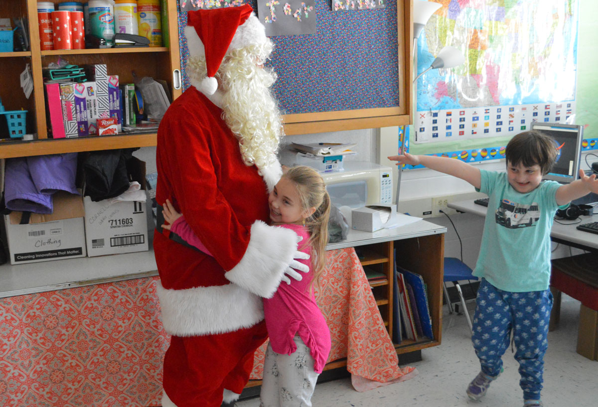Student hugs Santa Claus at Green Meadow