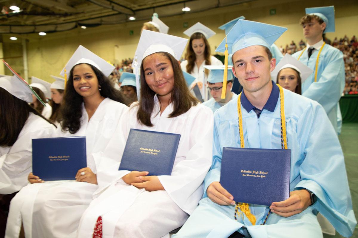 Columbia graduates holding their diplomas