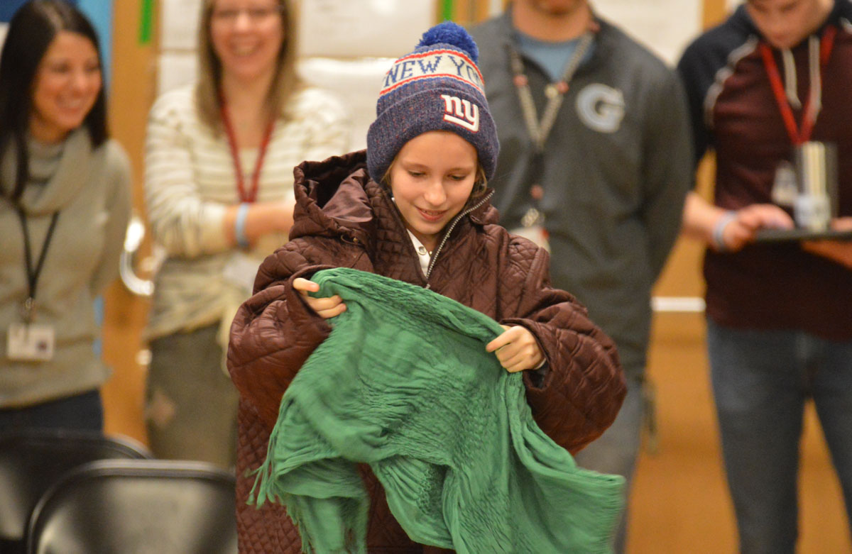 Student puts on winter clothes during relay race