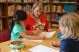 Sue Kralovic helps students with writing activity