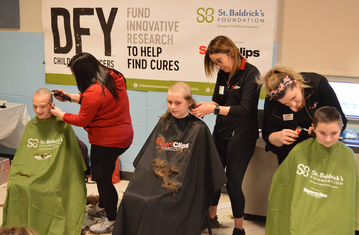 Students have their heads shaved as part of a fundraiser to benefit St. Baldrick's Foundation