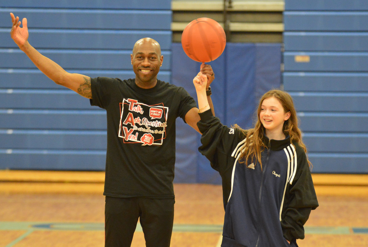 Tay Fisher helps student with basketball trick