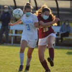 Soccer players battle for the ball