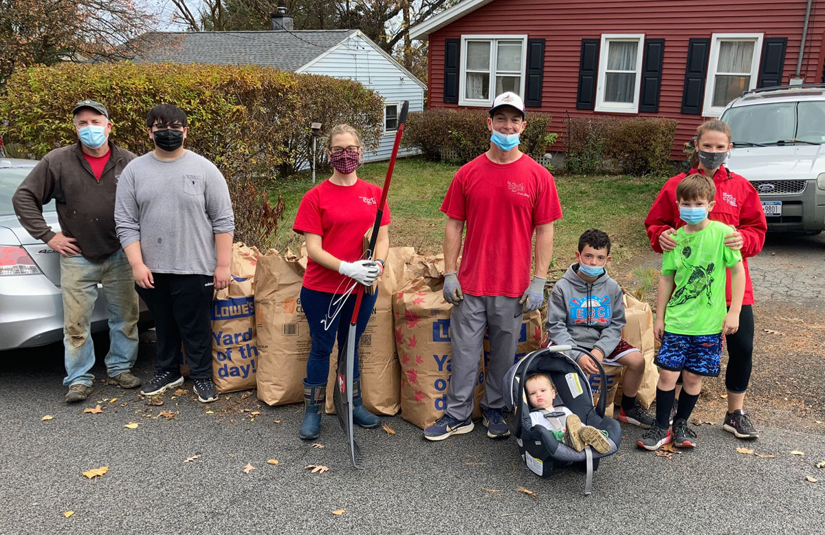 Teachers and students raking leaves