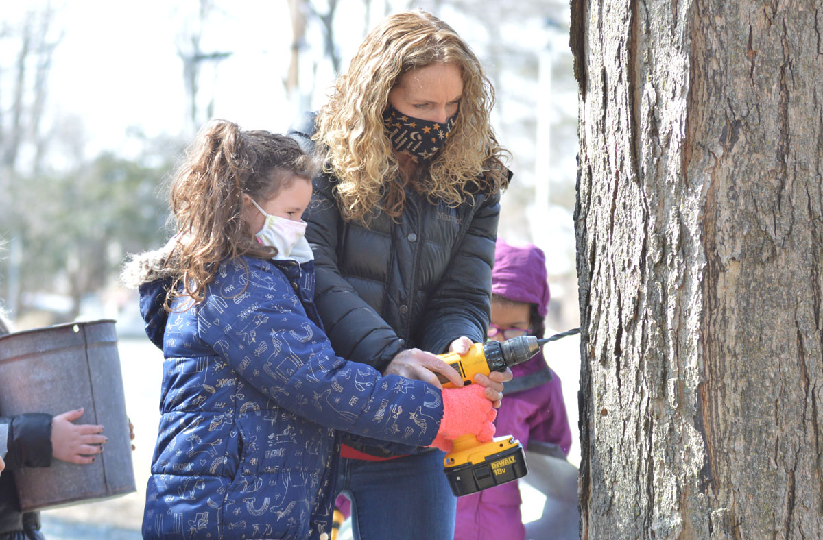 First grade teacher Melanie Lyte helps a student tap a maple tree at Bell Top Elementary School