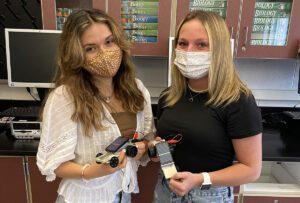 Emily Casatelli and Kayla Belanger holding solar cars