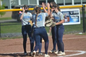 Softball players high five each other